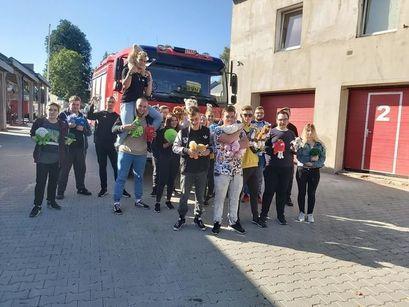 Uczniowie Zespołu Szkół w Żarowie z maskotkami przed remizą strażacką OSP w Żarowie.