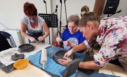 Uczestnicy warsztatów ceramicznych w Krukowie podczas lepienia rzeźb.
