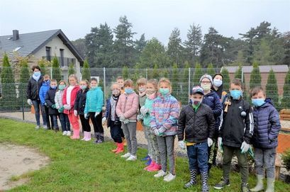 Uczniowie SP Żarów wraz z wychowawczynią na placu zielonym szkoły podczas sadzenia drzewek