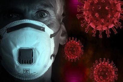 Na zdjęciu Pan w masce obok niego czerwone wirusy w tle