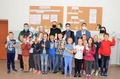 Uczniowie SP w Żarowie wraz z burmistrzem Leszkiem Michalakiem, zastępcą burmistrza Przemysławem Sikora, dyrektor szkoły Heleną Słowik i zastępcą dyrektora Adamem Ciupińskim z otrzymanymi butelkami ekologicznymi.