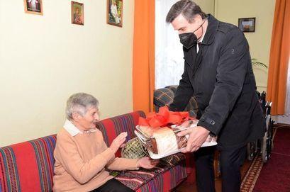 Burmistrz Leszek Michalak wręcza prezent na ręce stulatki