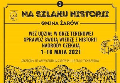 Plakat Na Szlaku Historii z napisami:  NA SZLAKU HISTORII - GMINA ŻARÓW WEŹ UDZIAŁ W GRZE TERENOWEJ SPRAWDŹ SWOJĄ WIEDZĘ Z HISTORII NAGRODY CZEKAJĄ 1-16 MAJA 2021 SZCZEGÓŁY NA WWW.CENTRUM.ZAROW.PL LUB FB.ME/GCKISZAROW