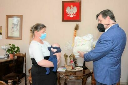 """Burmistrz Leszek Michalak wraz z Magdaleną Dąbrowską i jej synkiem podczas wręczenia pakietu """"Paka dla Niemowlaka"""""""