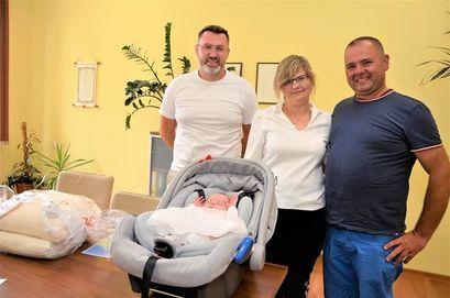 Zastępca Burmistrza Przemysław Sikora z rodzicami i dzieckiem podczas wręczenia pakietu Paka Dla Niemowlaka