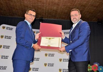 Wicemarszałek wręcza promesę zastępcy burmistrza Przemysławowi Sikorze