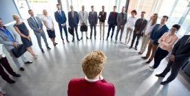 Osoby stojące w półkolu przed osobą w czerwonym swetrze