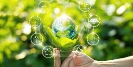 Dłoń na tle roślin, ikony odnawialnych źródeł energii krążące wokół ziemi.