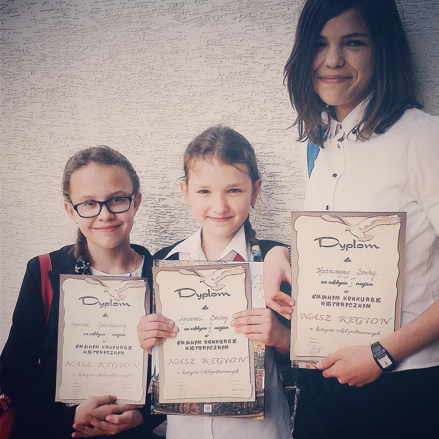 Dziewczynki pozujące do zdjęcia z dyplomami