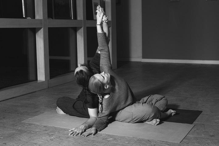Grafika przedstawia dwie siędzące kobiety podczas ćwiczeń