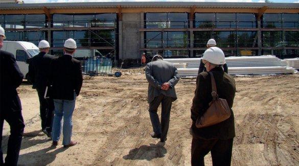 Ludzie w kaskach na placu budowy