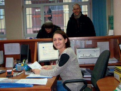 Pracownik urzędu trzymający dokument i dwie osoby stojące w tle