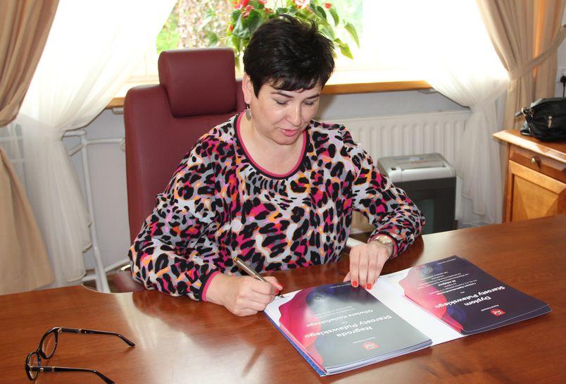 Starosta Danuta Smaga podpisuje dyplomy za osiągnięcia sportowe